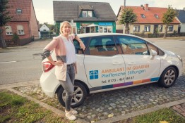 Sophie Schönemann vor Auto des ambulanten Pflegedienstes in Letzlingen