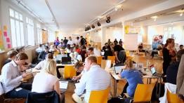 Junge Menschen sitzen in Gruppen und entwickeln gemeinsam digitale Lösungen